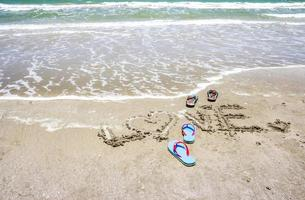 Slippers with love handwritten on the beach photo