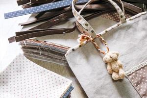 Bolsa de tela colgando oso muñeca sobre fondo de madera foto
