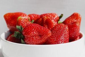 Fresas frescas en un recipiente sobre un fondo blanco. foto
