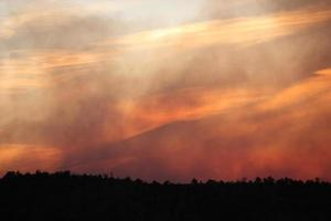 Transluscent layers of smoke and clouds in sky at sunset during a forest fire photo