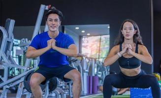 beautiful Asian woman is exercising in a gym with a personal trainer  handsome man Fitness photo