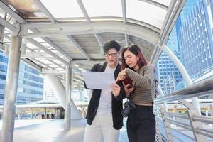 Asian tourists are check information on accommodation and attractions during  concept of living a happy couple photo