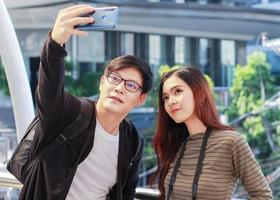 Young Asian tourists are using smart phones selfie During a visit to Thailand  concept of living a happy couple photo