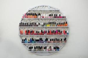 Nail salon wall with colorful nail polish bottles photo