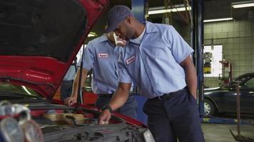 twee automonteurs kijken samen naar auto video