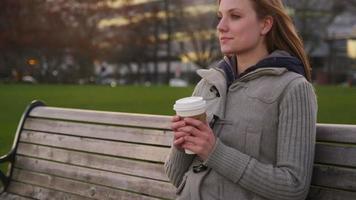 ung kvinna sitter på parkbänken med kopp kaffe video