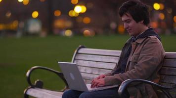 junger Mann sitzt auf einer Parkbank mit Laptop-Computer video