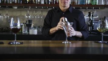 Camarero haciendo un martini en el bar. video