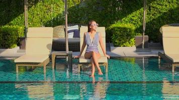 Asian woman relax and enjoy around outdoor swimming pool video