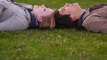 giovane coppia, posa, in, erba, indicare, a, clouds video