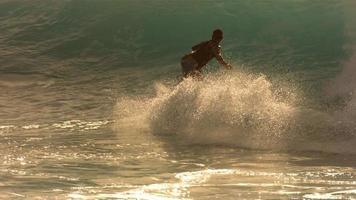 surfare rider vinkar i sent på eftermiddagen ljus, slow motion video