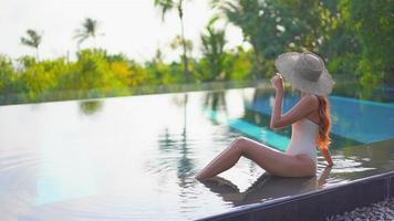Mujer asiática relajarse y disfrutar de la piscina al aire libre video