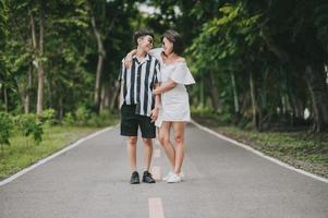 Feliz pareja de lesbianas lgbt asiáticas enamoradas pasando un buen rato de pie y abrazándose en el parque foto