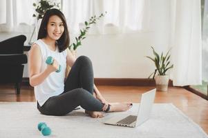 Hermosa mujer asiática sana sentada en el suelo sosteniendo mancuernas usando el portátil en casa en la sala de estar listo para entrenar en línea foto