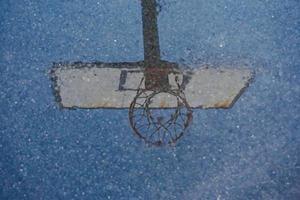 Aro de baloncesto callejero reflejado en el charco foto