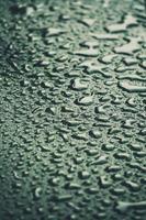 Gotas de lluvia sobre el fondo de textura de suelo gris foto