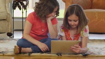 två unga flickor som använder den digitala minnestavlan tillsammans video