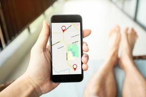 Man hand holding smartphone with GPS map to route destination photo