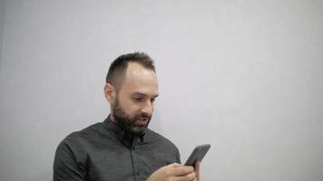 ein mann in hemd und bart schreibt sms video