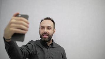 um homem com barba faz uma selfie ao telefone video