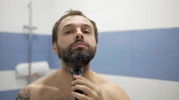 Bearded man shaving trimmer video