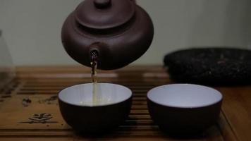 man giet thee uit een aardewerken theepot in kommen video