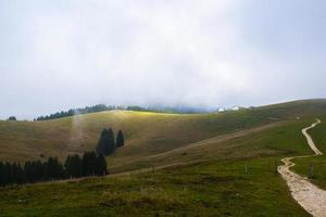 Cloudy sky above green hills photo