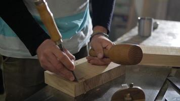 A man works a chisel and a mallet video