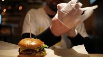 l'homme avec une barbe porte des gants pour manger un hamburger video