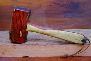 Martillo de mazo de madera de palisandro y herramienta hecha a mano de Tailandia para ser utilizada por un carpintero en el taller en el antiguo banco de trabajo foto