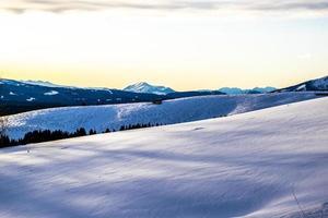 colinas nevadas y amanecer foto