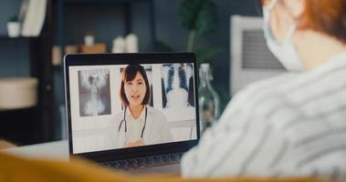 Young Asia girl wear protective face mask using laptop talk about disease in video call with senior doctor online consultation in living room at house photo