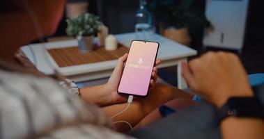 Joven y atractiva dama de Asia usar auriculares usando el teléfono para escuchar música digital canal en línea de podcasts sentarse en el sofá en la sala de estar por la noche foto