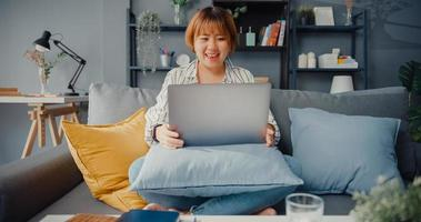Asia businesswoman using laptop talk to colleagues about plan in video call while working from house at living room photo