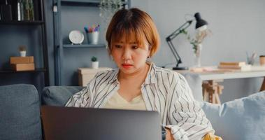 Señora independiente de Asia siente dolor de cabeza mientras está sentado en el sofá con el portátil en línea aprender en el salón de la casa foto
