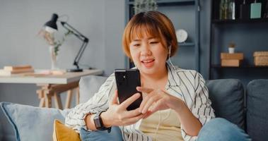 Young Asia lady using smart phone video call talk with family on sofa in living room at house photo