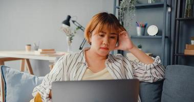 Freelance Asia lady feel headache while sitting on couch with laptop online learn in living room at house photo