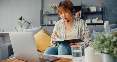 Asia empresaria usando laptop hablar con colegas sobre el plan en videollamada mientras trabaja desde casa en la sala de estar foto