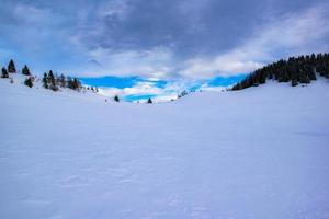 Snowy hill and blue sky with clouds photo