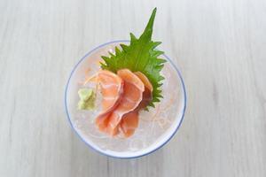 Salmon slice or salmon sashimi in Japanese style fresh serve on ice with fresh wasabi photo