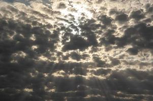Beautiful black stormy clouds with sunbeams photo