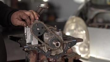 O mestre do carro controla a corrente do eixo de comando do motor do carro reformado na oficina video