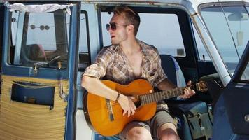 Guy sitting in van playing guitar on road trip video