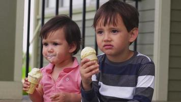 Young brother and sister eating ice cream on porch video