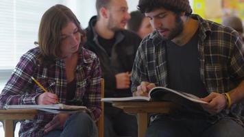 estudantes universitários sentados em sala de aula estudando video