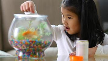 Young Asian girl feeding fish in bowl video
