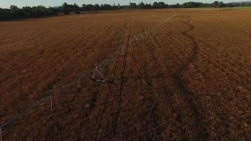 Aerial shot of irrigation equipment in field at sunrise video