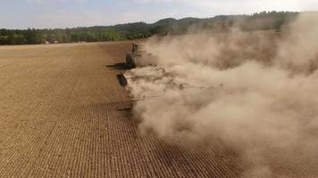 Tractor plowing dusty field aerial view video