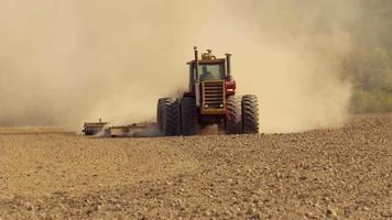 Tractor plowing field in slow motion video