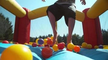 Boy bouncing in inflatable play house, super slow motion video
